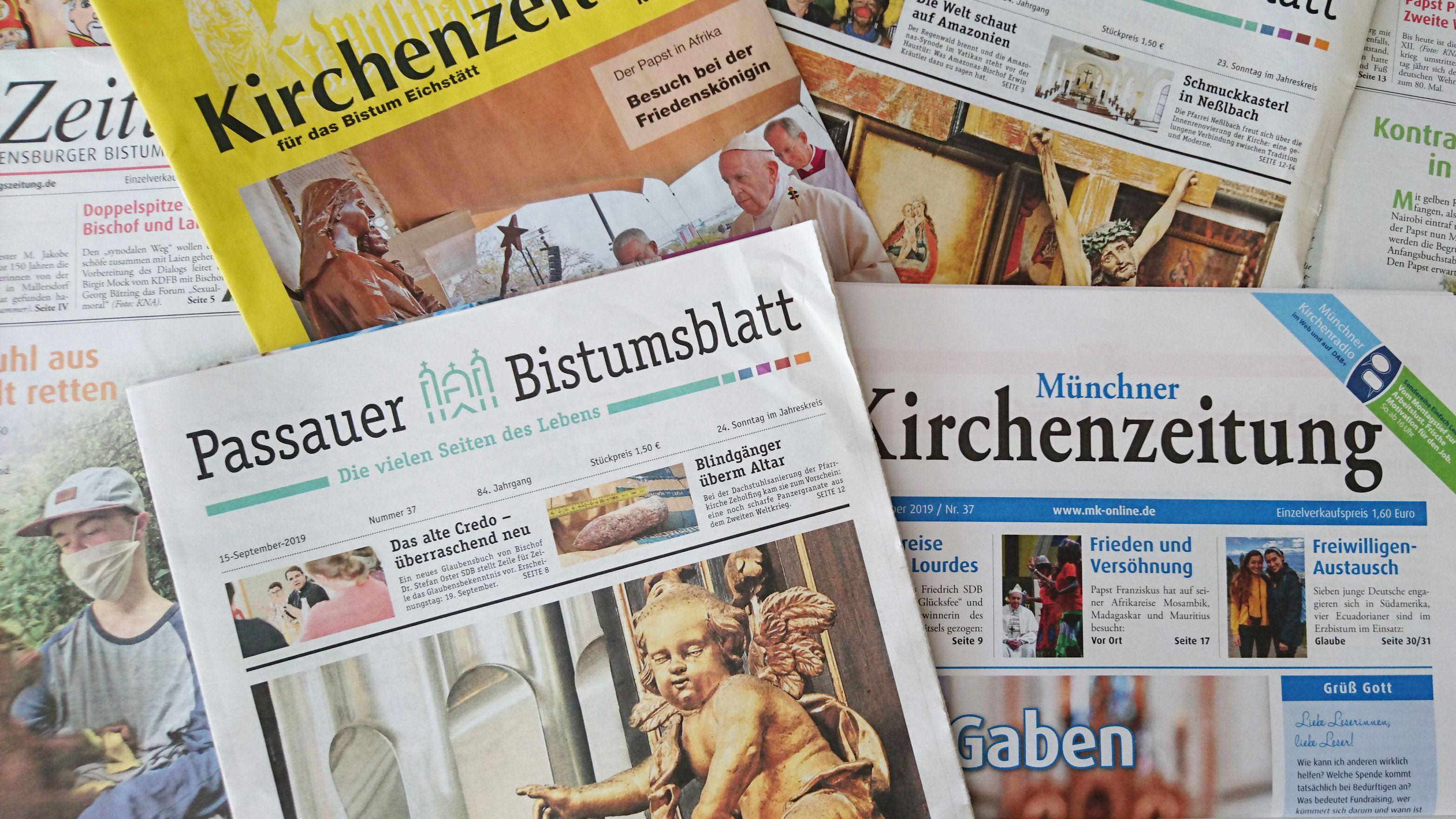 Bayerische Kirchenzeitungen liegen auf- und nebeneinander: Titelseiten der Münchner Kirchenzeitung, des Passauer BIstumsblatts, der Kirchenzeitung für das Bistum Eichstätt und der Regensburger Sonntagszeitung.