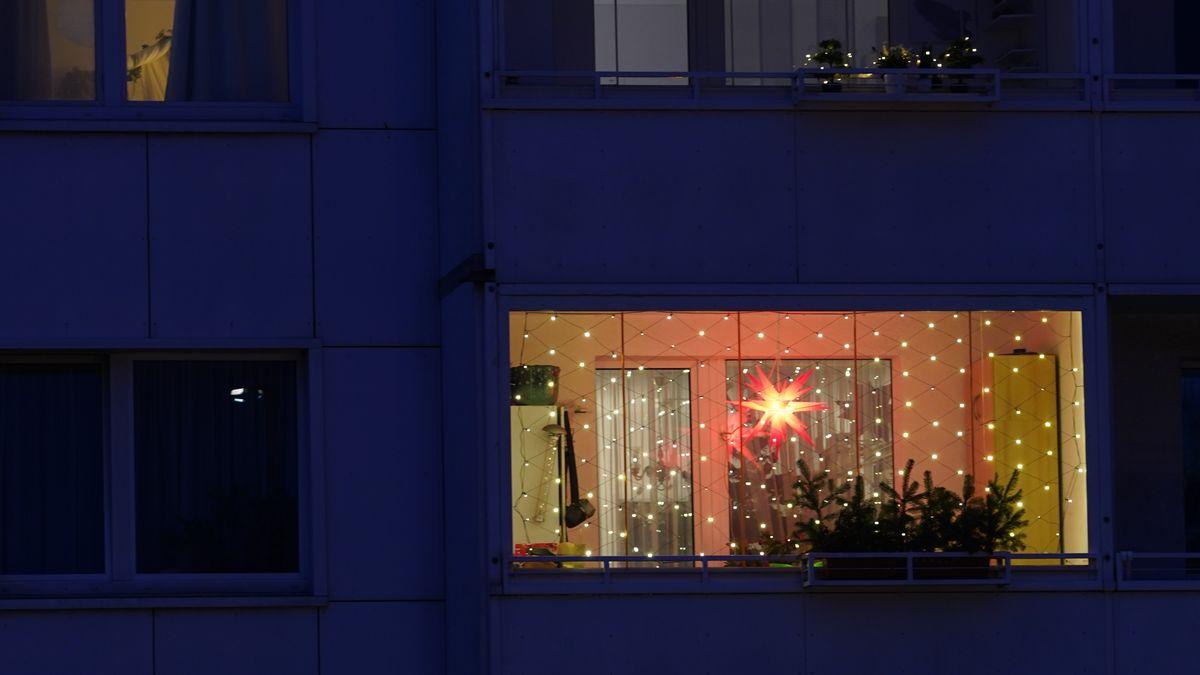 Weihnachtsstern leuchtet auf einem Balkon.