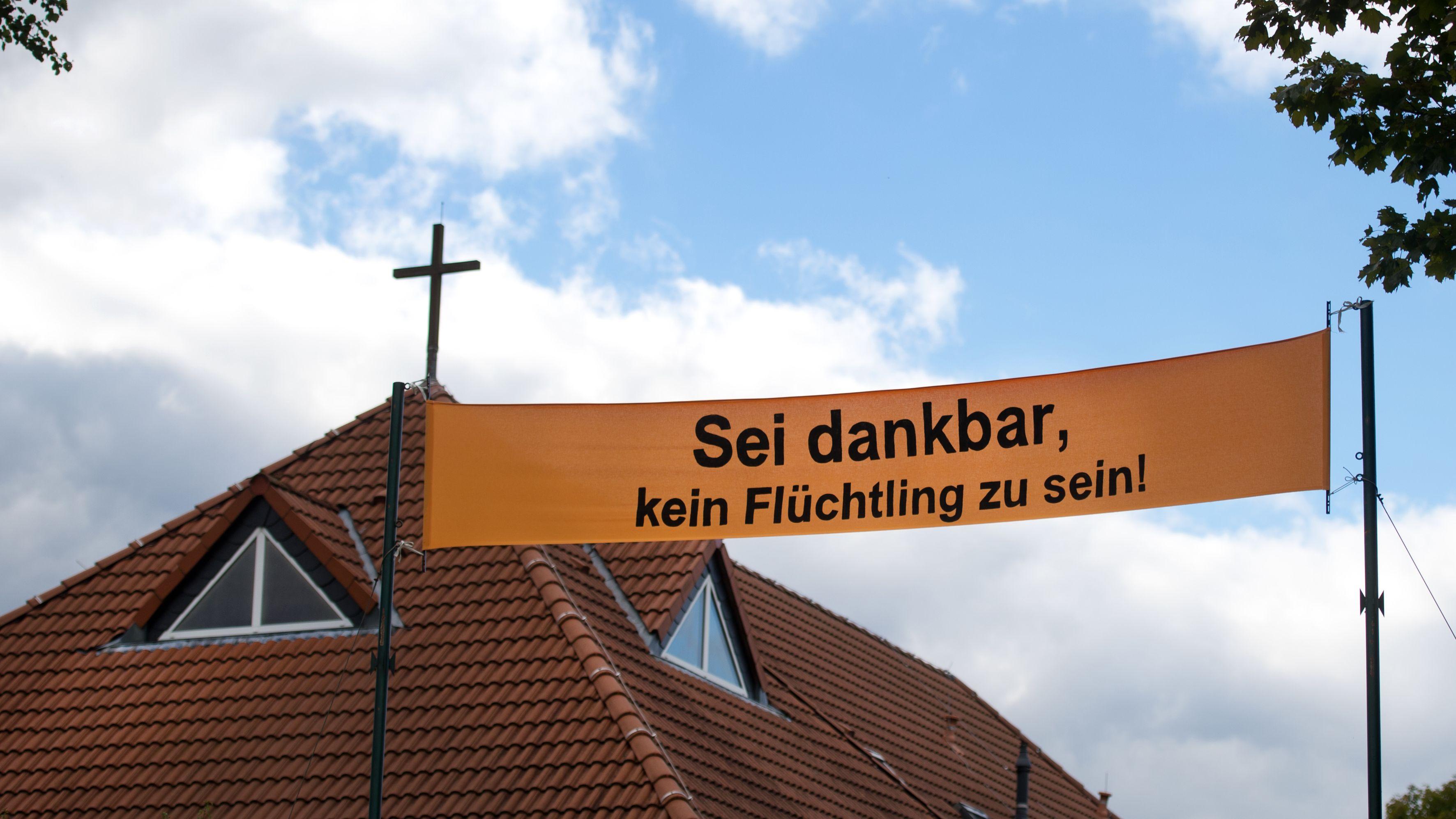 """Banner vor einer Kirche: """"Sei dankbar, kein Flüchtling zu sein!"""" (Symbolbild)"""