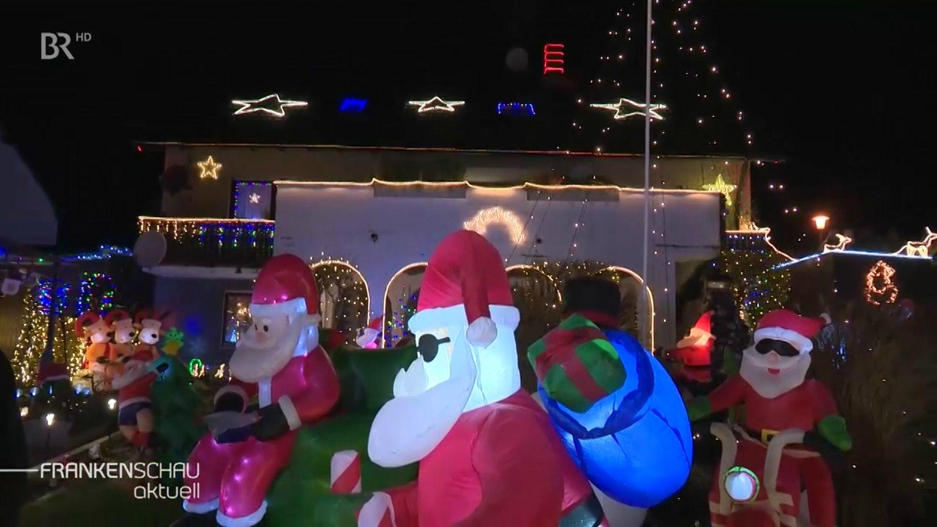 Leuchtende Nikoläuse stehen in einem Garten vor einem weihnachtlich geschmückten Haus.