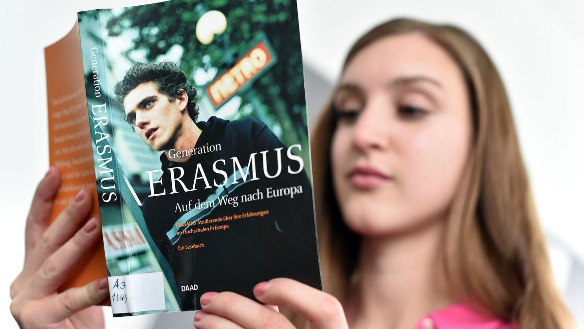 Studentin hält ein Buch über das Erasmus-Austausch-Programm in der Hand