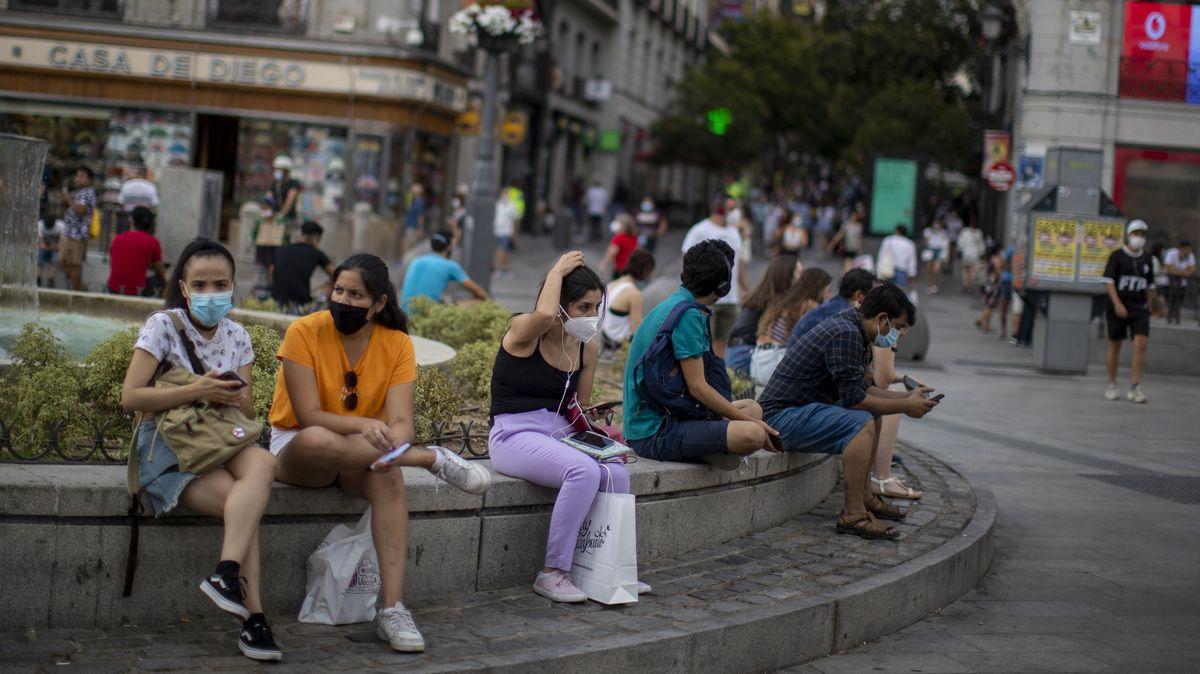 Menschen mit Masken sitzen in Madrid auf einer Straßenbank
