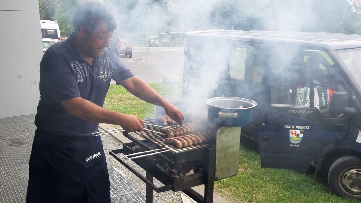 Ein Mann grillt Bratwürste.