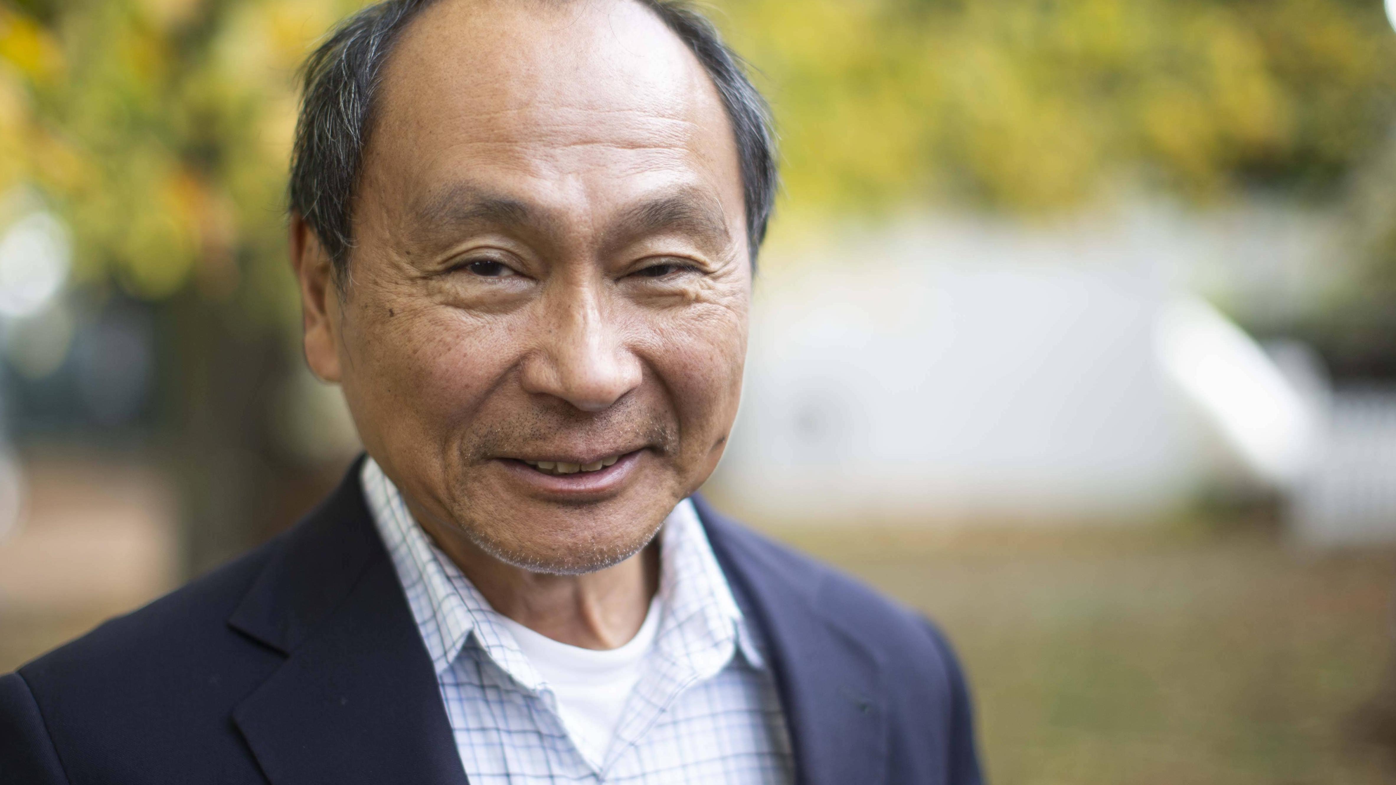 Francis Fukuyama lächelt, im Freie stehend, in die Kamera