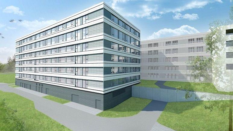 Ein Modell des neuen Bettenhauses ist sieben Stockwerke hoch, davor grüne Rasenflächen