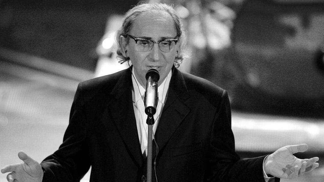 Ein Mann in schwarzem Anzug steht vor einem Mikrofon.