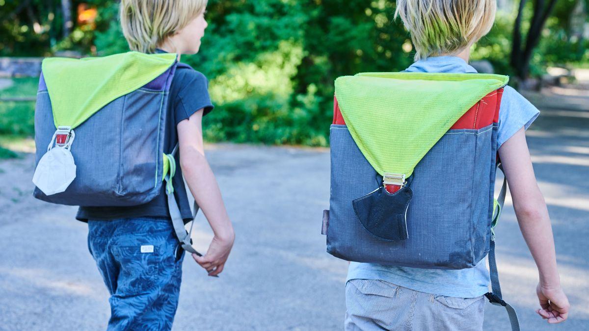 Zwei Grundschüler mit Masken am Schulranzen (Symbolbild)