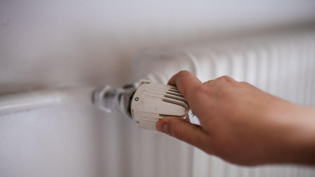 Eine Hand dreht am Thermostat
