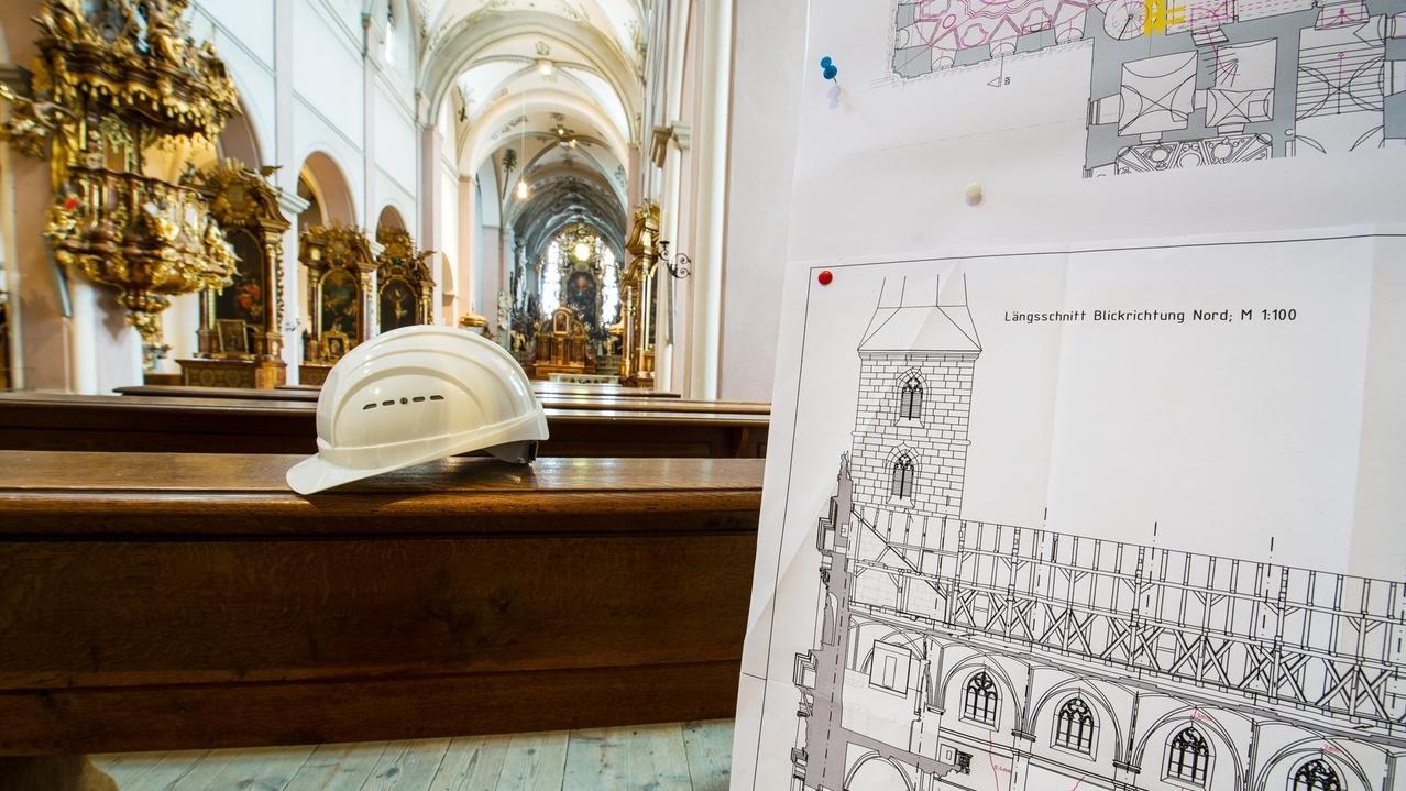 Innenraum der St. Michael-Kirche in Bamberg. Auf einer Kirchenbank liegt ein Baustellenhelm. Daneben steht der Plan des Architekten.
