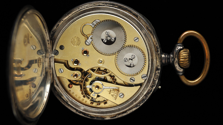 Symbolbild: Uhrwerk einer alten silbernen Taschenuhr