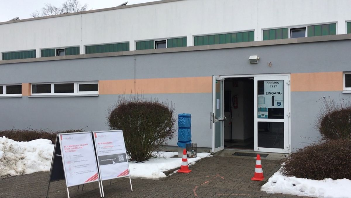 Vor einem Flachbau mit geöffneter Tür steht ein Hinweisschild, das den Weg zur mobilen Teststation weist.
