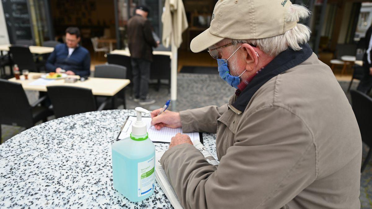 Ein Gast gibt seine Daten in einer Liste eines Restaurants ein