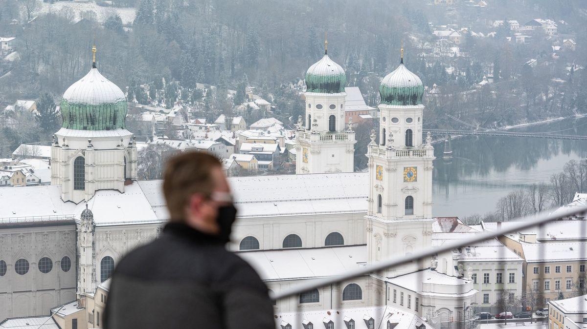 Ein Mann mit Corona-Maske blickt auf das winterliche Passau