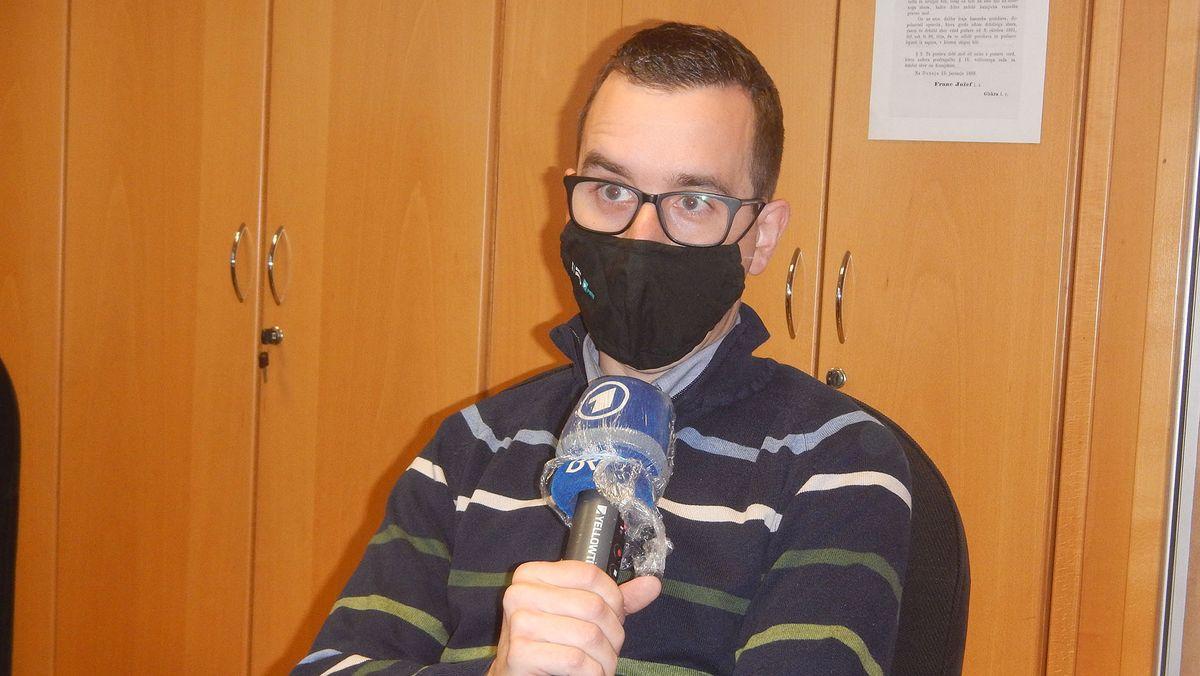 Danijel Poslek beim Interview sitzend vor einer Regalwand.