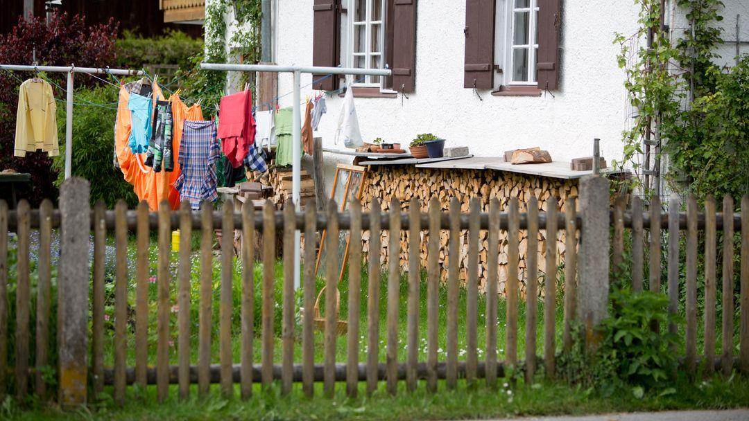 Ein Gartenzaun auf dem Land, dahinter ist ein Rasen mit einer vollgehängten Wäscheleine und ein Holzstapel vor einem Haus mit Fensterläden