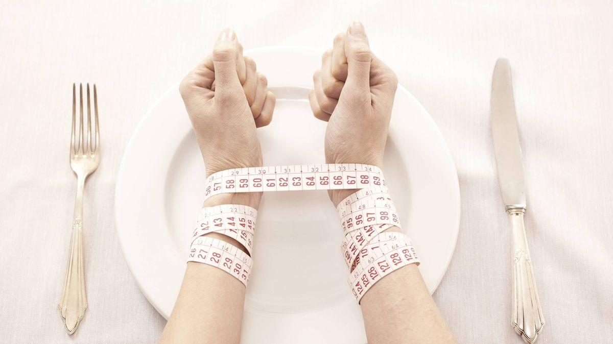 Hände liegen auf einem Teller und sind mit einem Maßband gefesselt