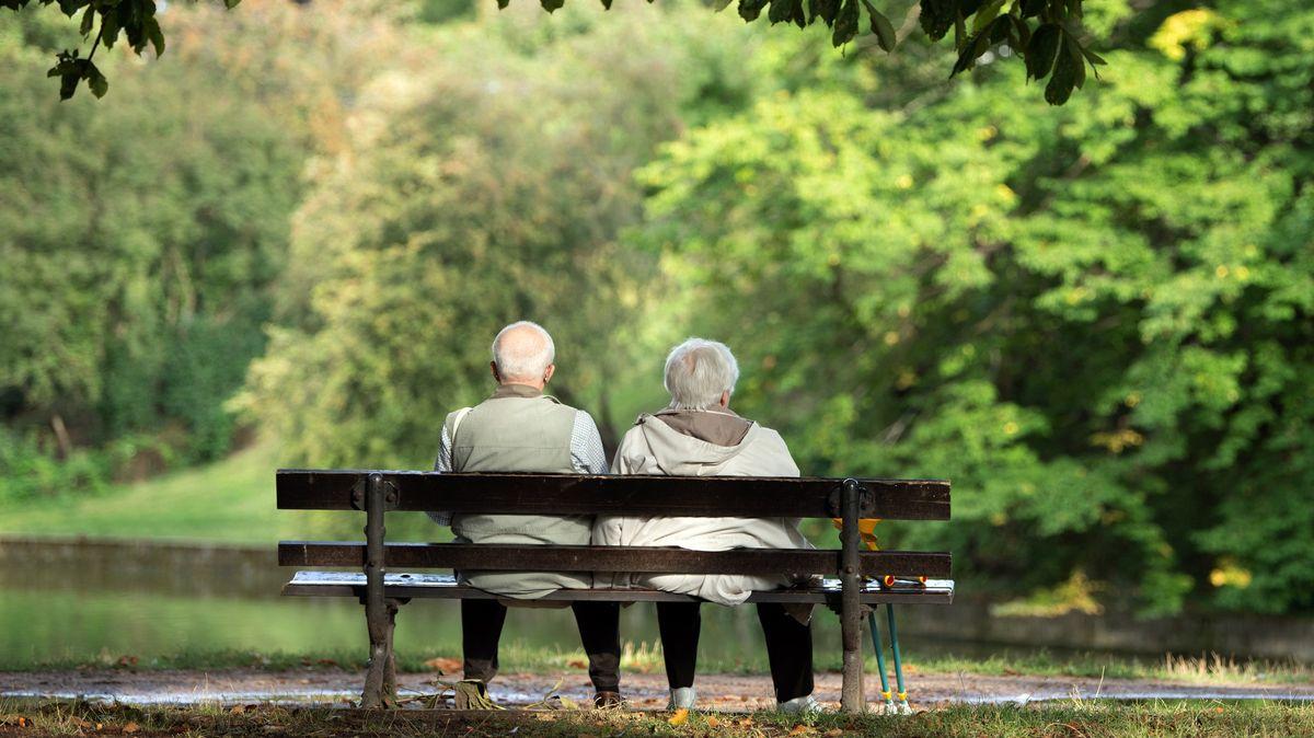 Eine Seniorin und ein Senior sitzen auf einer Bank.