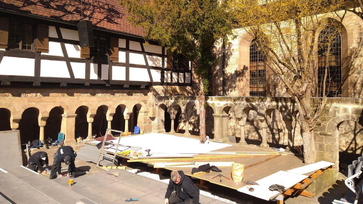 Handwerker montieren eine Bühne im ehemaligen Kloster.