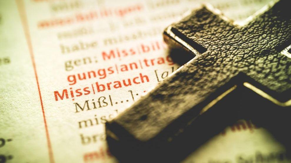 Symbolbild sexueller Missbrauch: Ein Kreuz liegt auf der Seite eines Wörterbuchs.