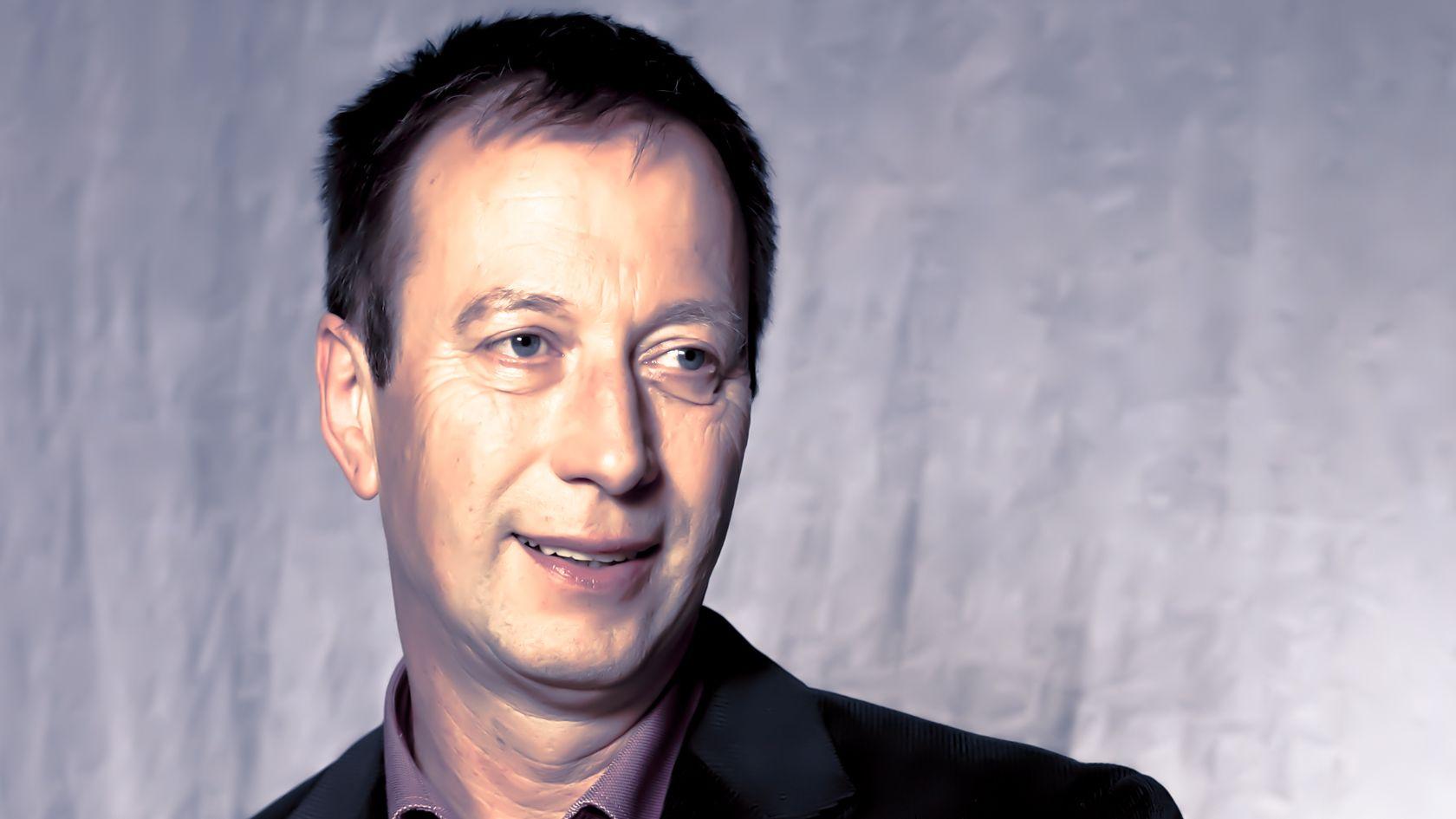 Schriftsteller Hans Pleschinski blickt lächelnd nach rechts aus dem Bild heraus