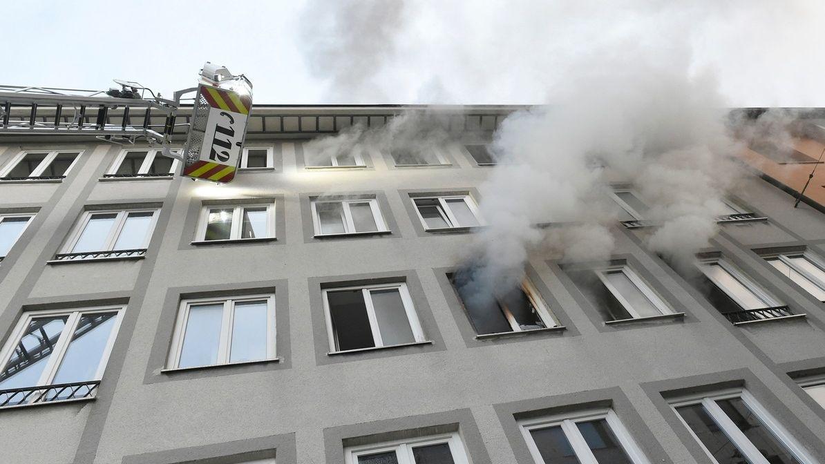 Rauch dringt aus den Fenstern eines Mehrfamilienhaus im Münchner Stadtteil Lehel; Drehleiter der Berufsfeuerwehr.