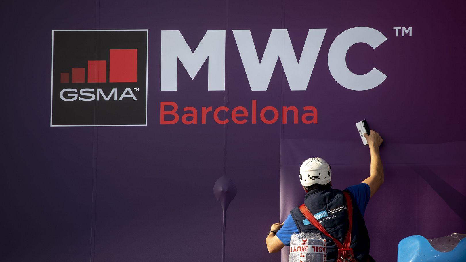 Arbeiter befestigt MWC Plakat