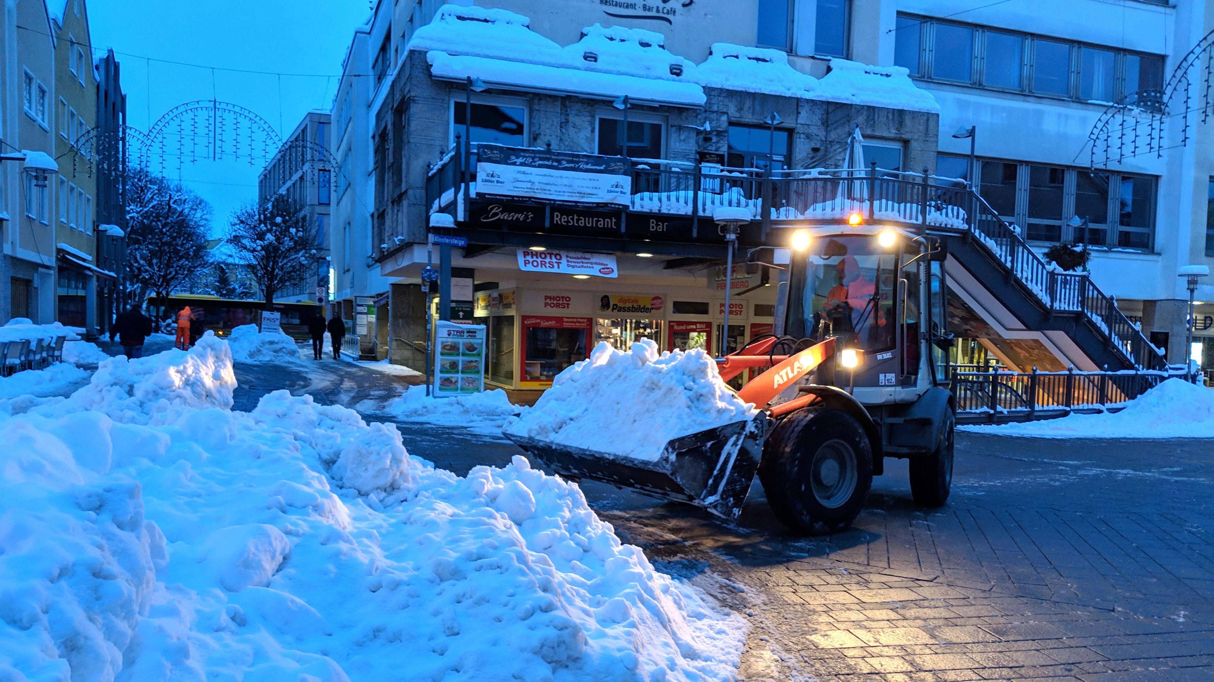 Winterdienstfahrzeug vor Schneehaufen in Kemptener Fußgängerzone