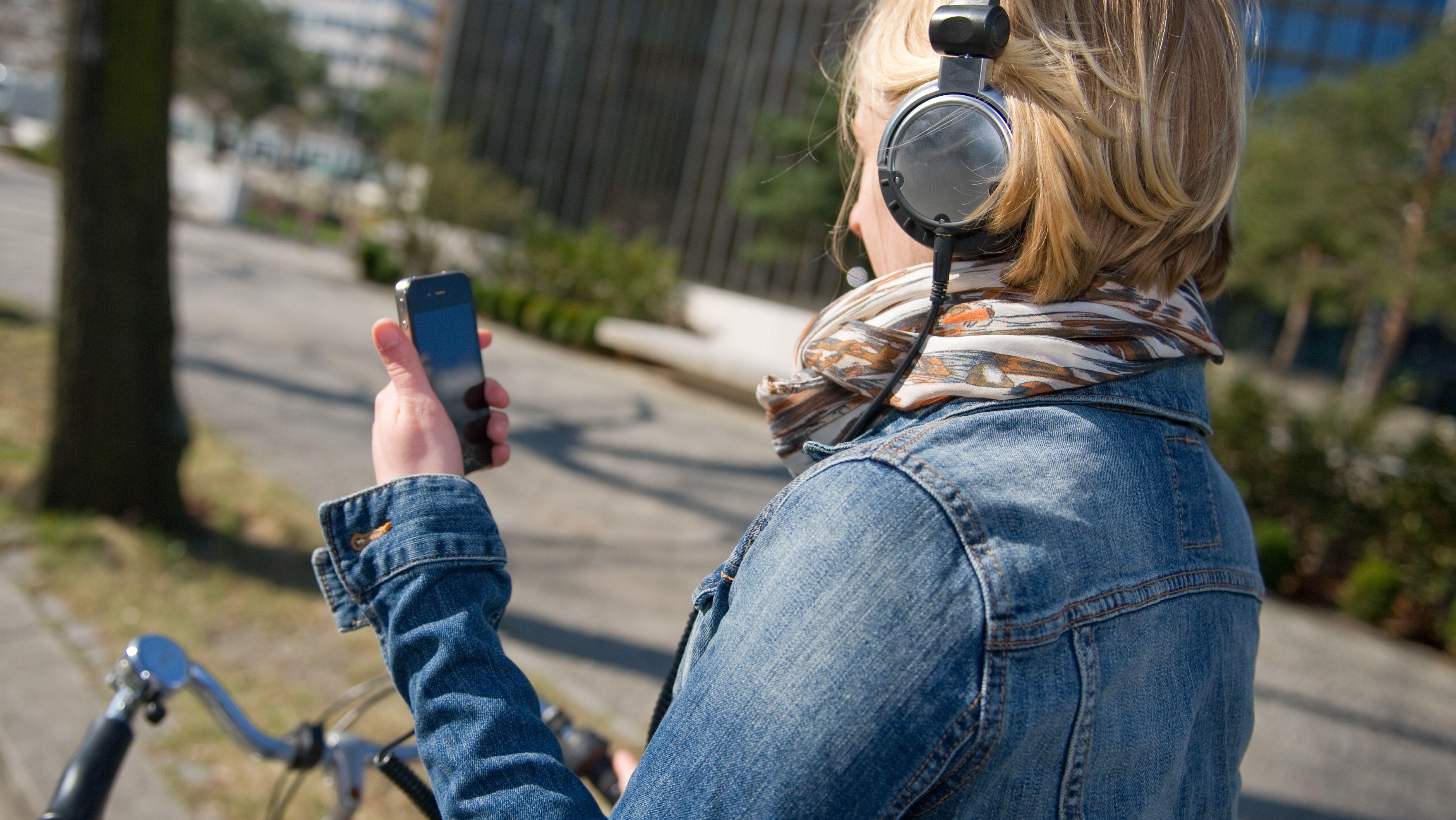 Eine Frau fährt mit Kopfhörern und Smartphone in der Hand auf einem Fahrrad
