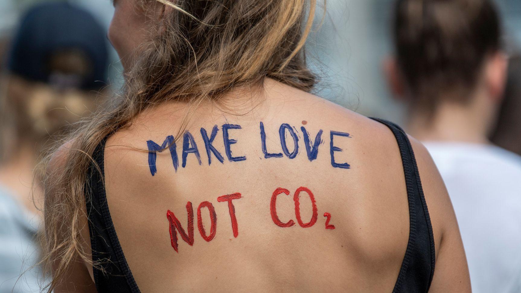"""Auf dem Rücken einer jungen Frau steht: """"Make Love, Not CO2""""."""