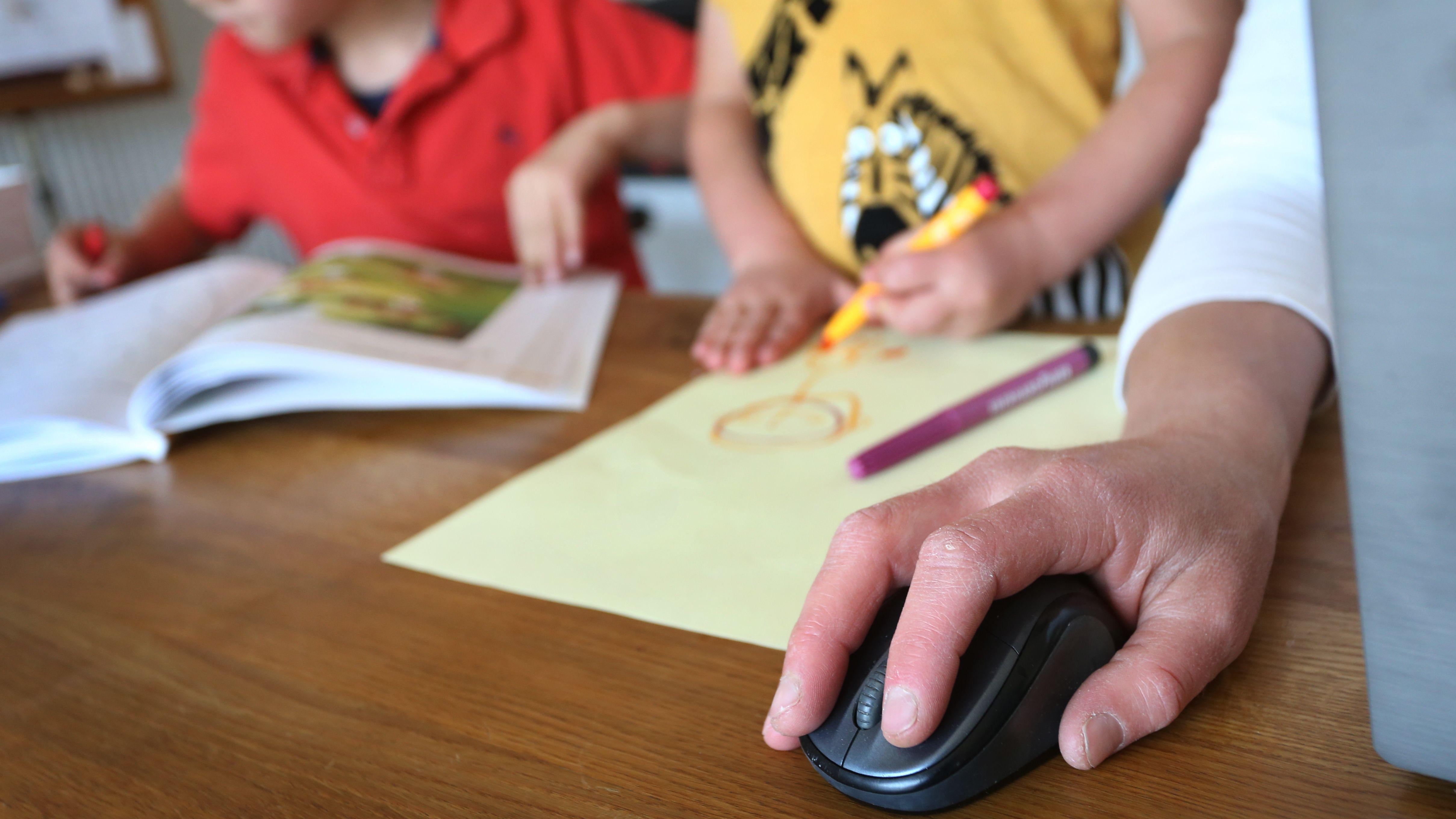 Eine Mutter arbeitet Zuhause an ihrem Laptop, während ihre Kinder neben ihr malen und ein Buch ansehen.