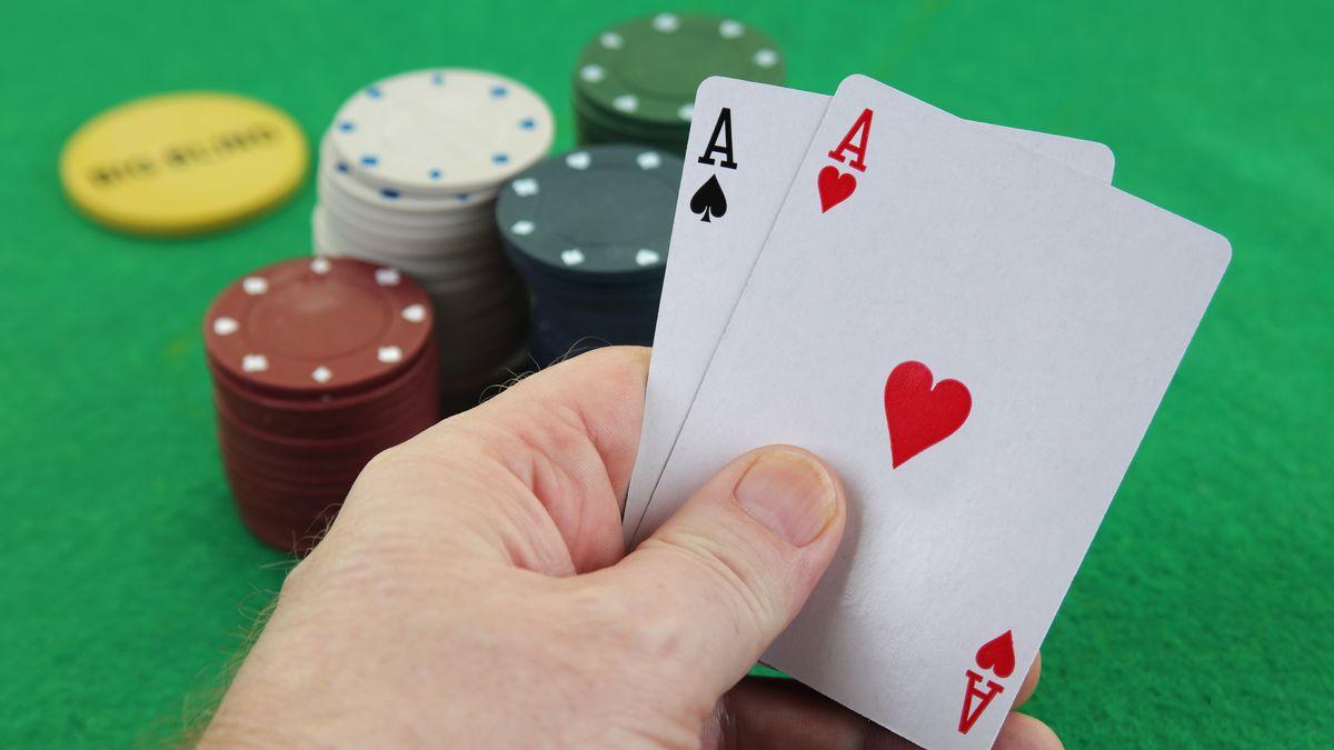 Eine Hand hebt zwei Asse (Symbolbild).