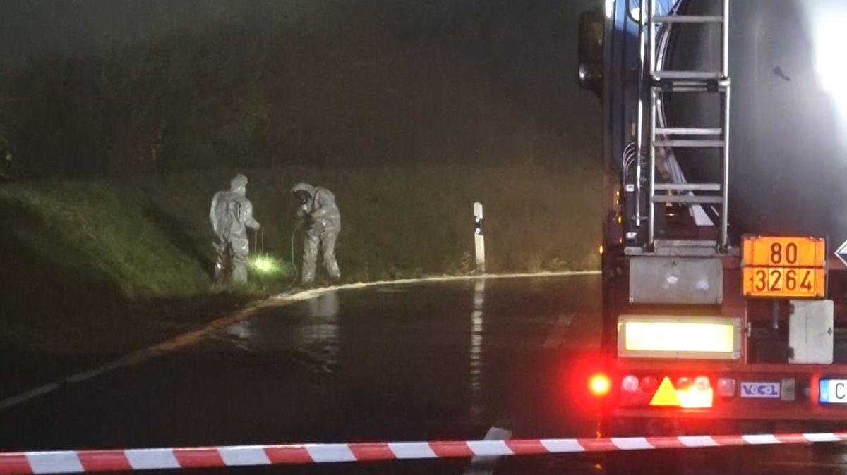 Ein Tankzug steht nachts auf einem Rastplatz. Einsatzkräfte in Schutzanzügen binden einen ausgelaufenen Gefahrenstoff.