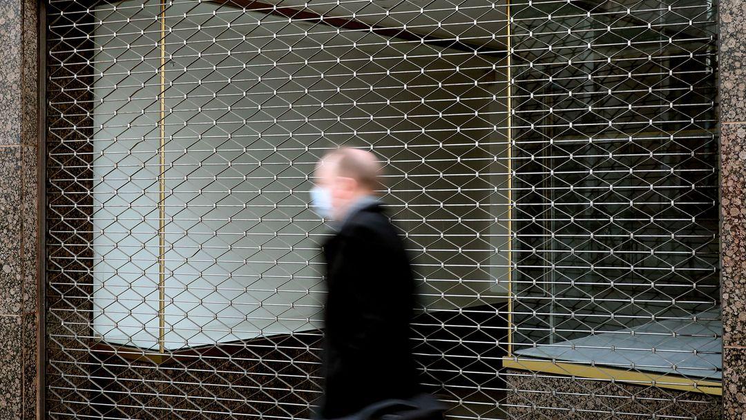Ein Mann der eine Mund-Nasen-Bedeckung trägt, geht an einem leerstehenden Laden vorbei.