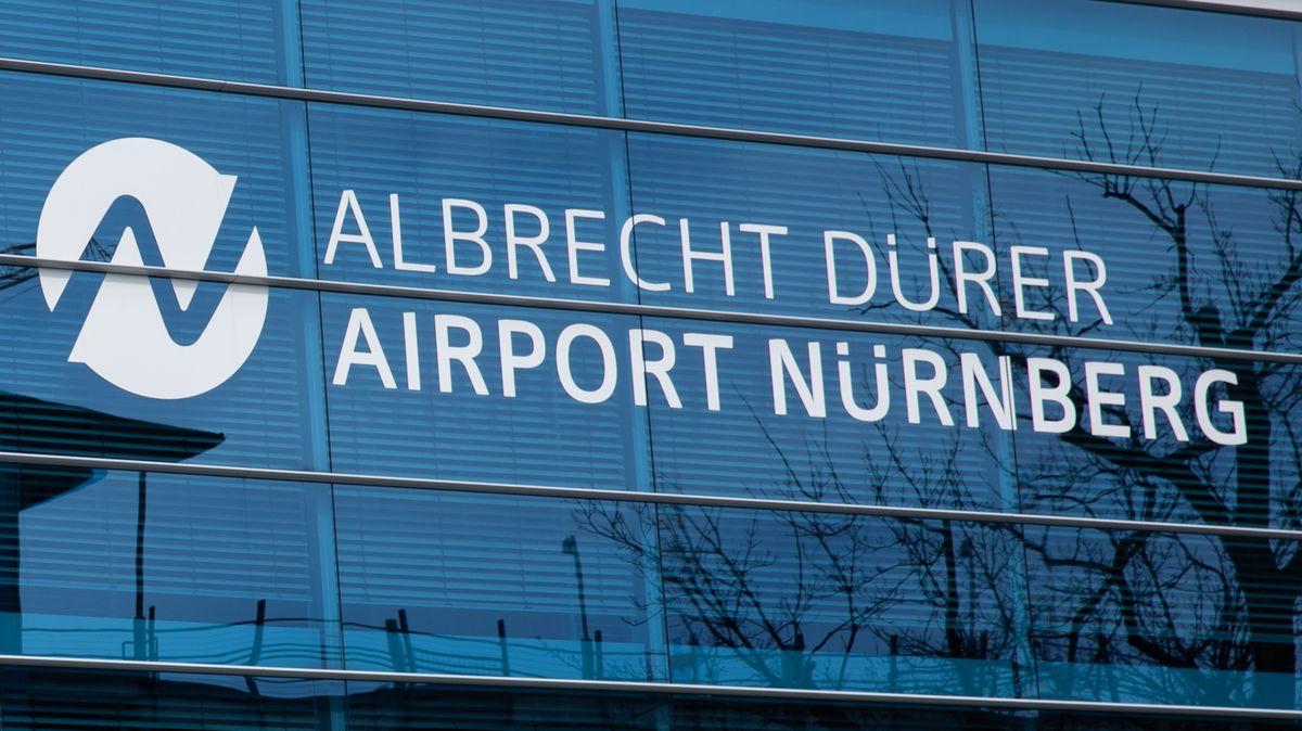 """Gläserner Eingangsbereich des Nürnberger Flughafens mit der Aufschrift """"Albrecht Dürer Airport Nürnberg"""""""