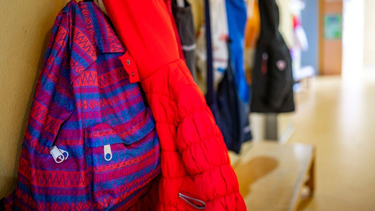 An einer Garderobe in einem Kindergarten hängen Jacken und Rucksäcke von Kindern.