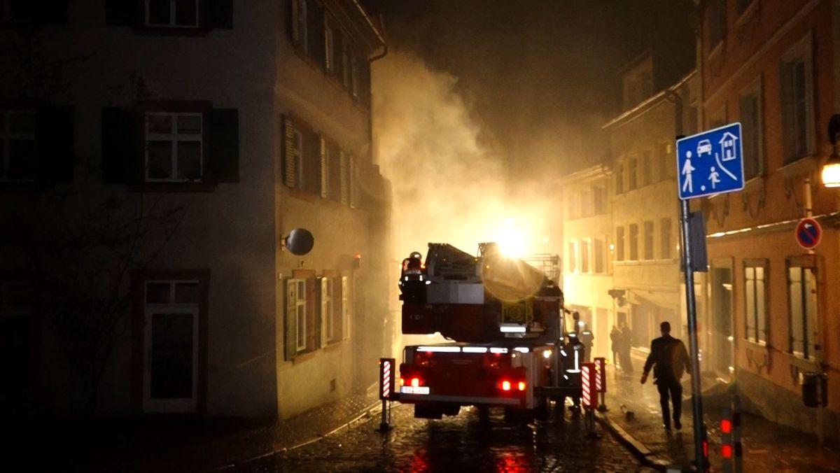In einer Gasse steht ein Feuerwehrauto im Gegenlicht, dass von Qualm eingehüllt ist.