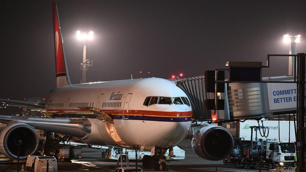 Ein Charterflugzeug steht an einem Terminal des nächtlichen Frankfurter Flughafens