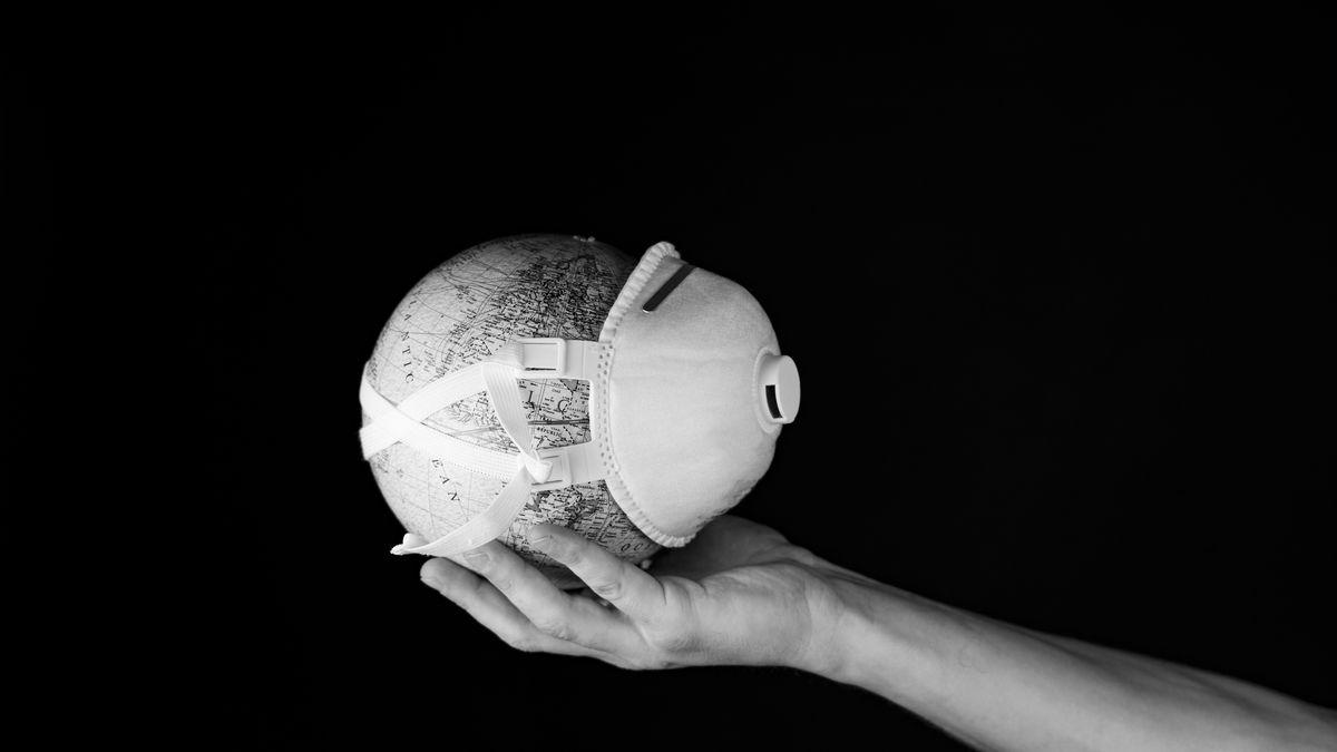 Schwarzweiß-Foto einer Hand, die einen kleinen Globus mit einer Mund-Nasen-Maske hält.