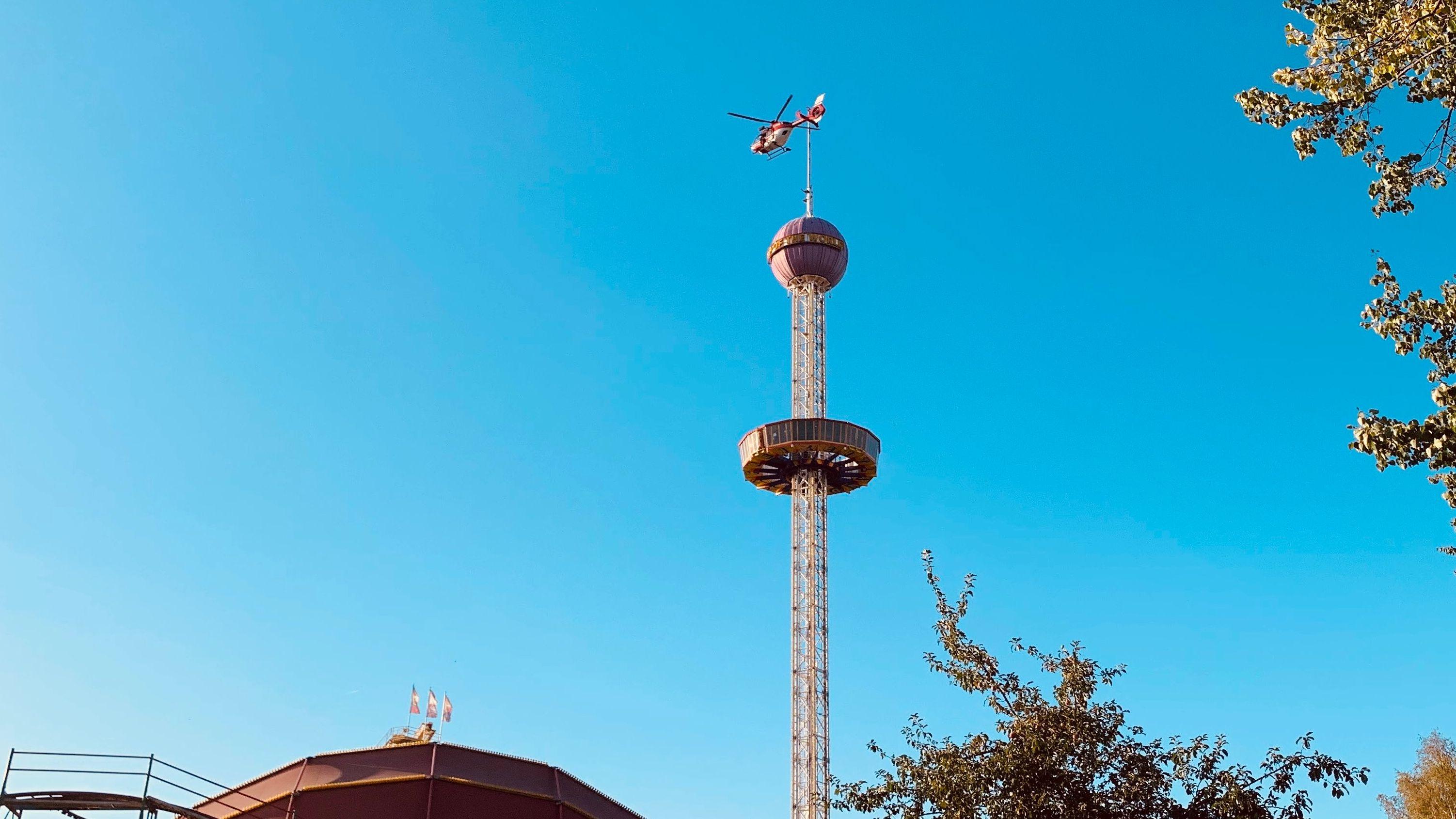 Ein Hubschrauber fliegt über einem Aussichtsturm im Freizeitland Geiselwind.