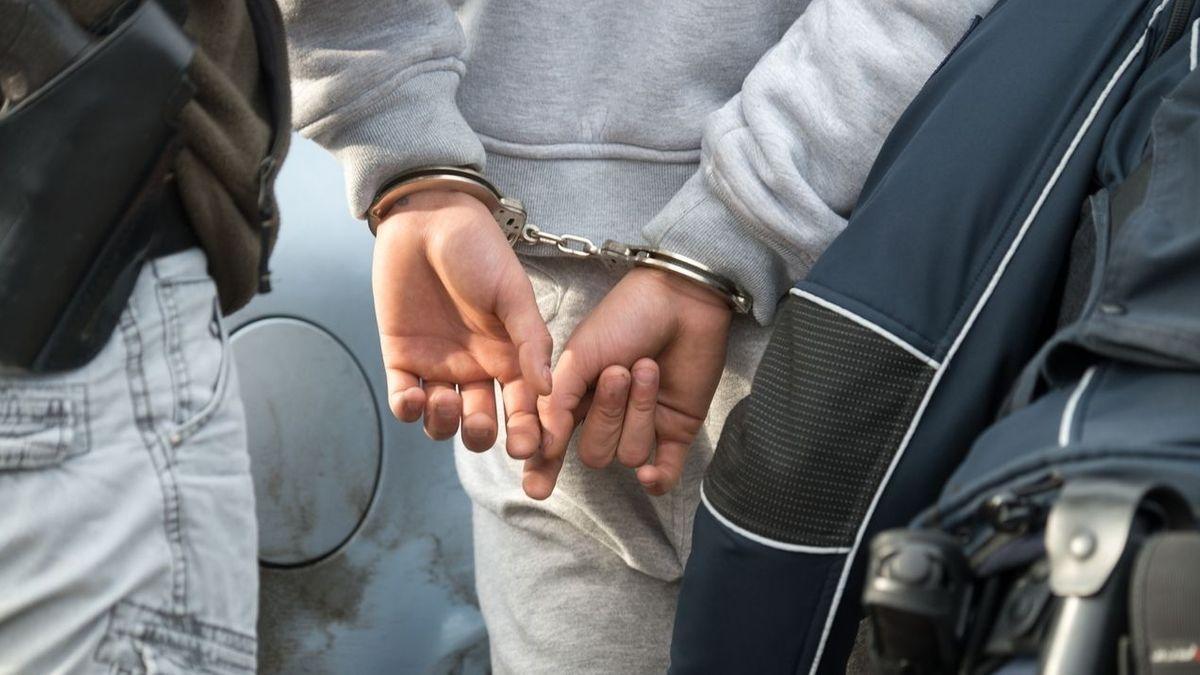 Ein junge Mann mit Handschellen auf dem Rücken wird von zwei Polizeibeamten abgeführt.