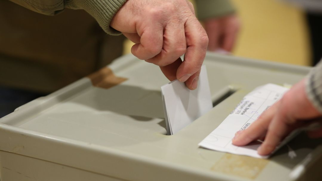 Hände an einer Wahlurne