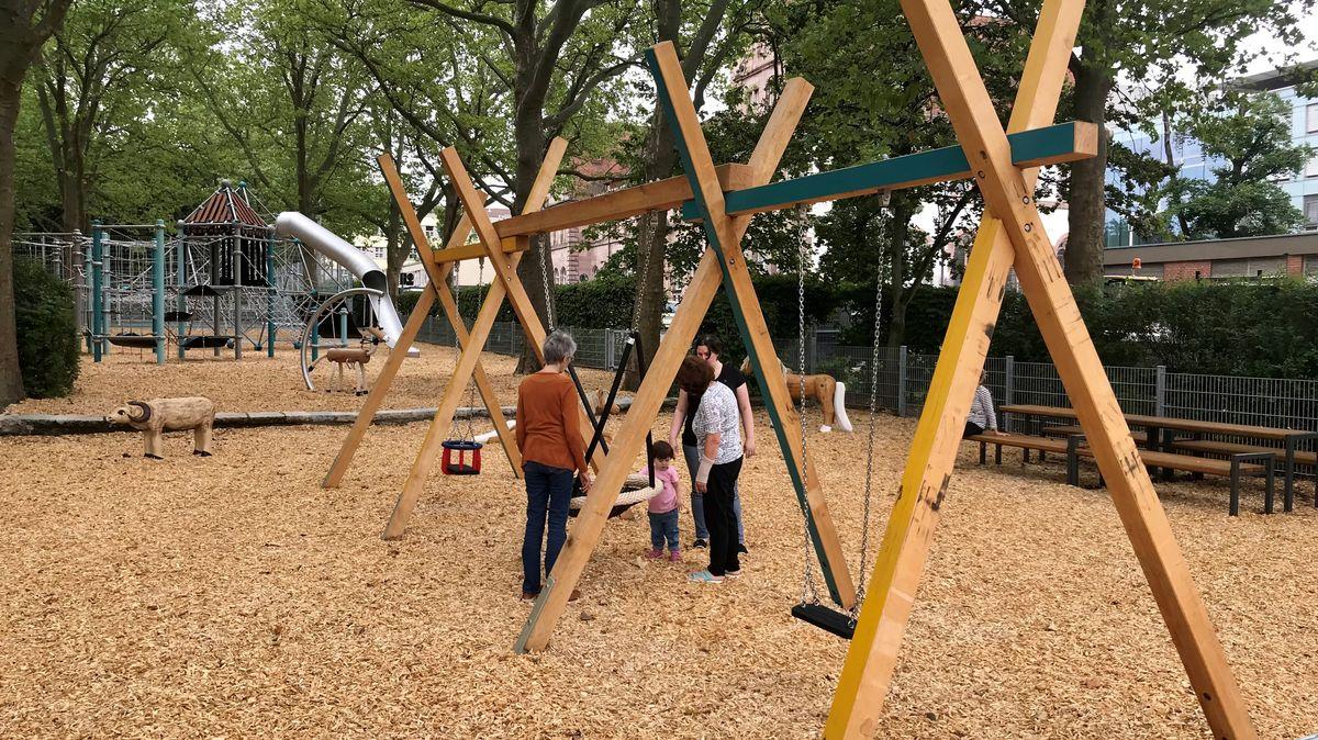 Menschen auf dem Spielplatz mit Schaukeln, Klettergerüsten und einer Rutsche.