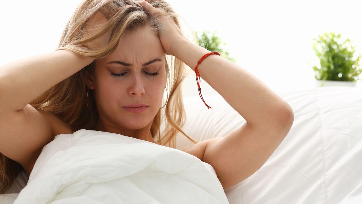 Frau im Bett, die sich die Haare rauft