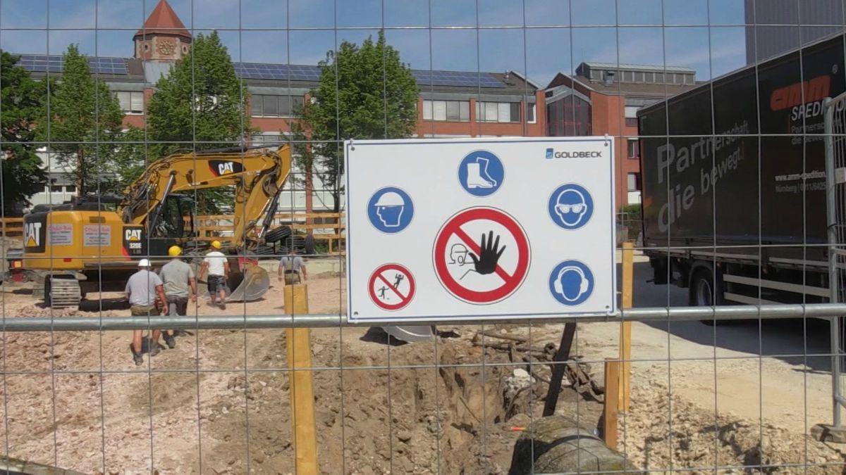 Baustellenzaun und Baustelle mit Bagger