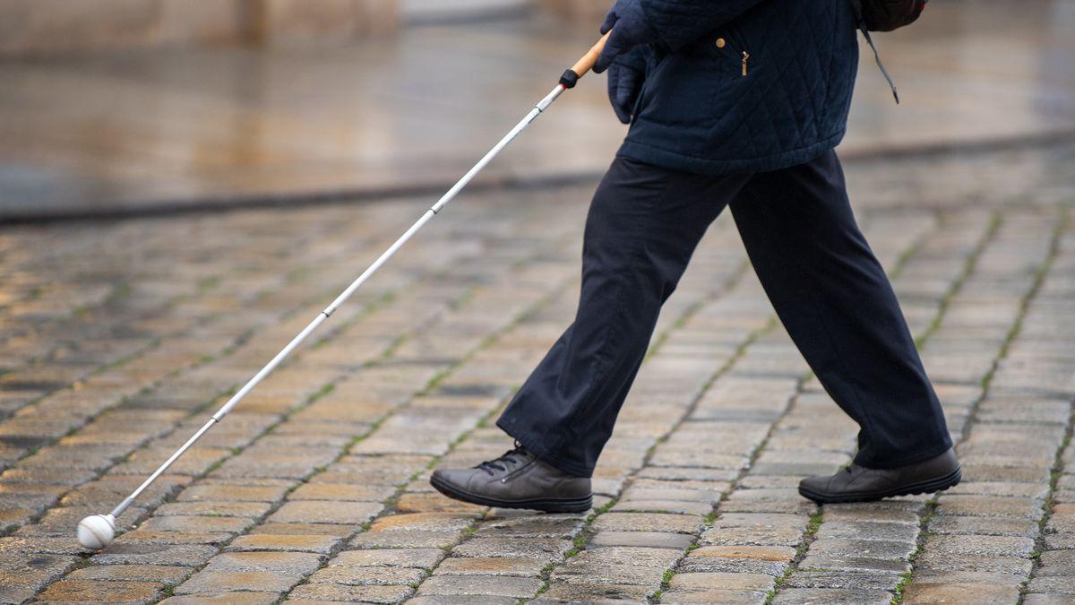 Mann mit Blindenstock geht über Kopfsteinpflaster.