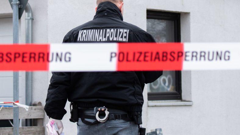 Ein Kriminalpolizist an einer Polizeiabsperrung