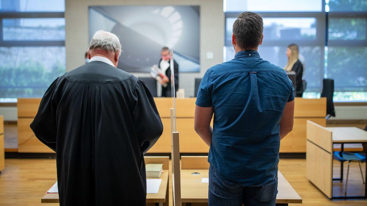 Der angeklagte Polizeischüler und sein Anwalt stehen in Würzburg in einem Gerichtssaal.