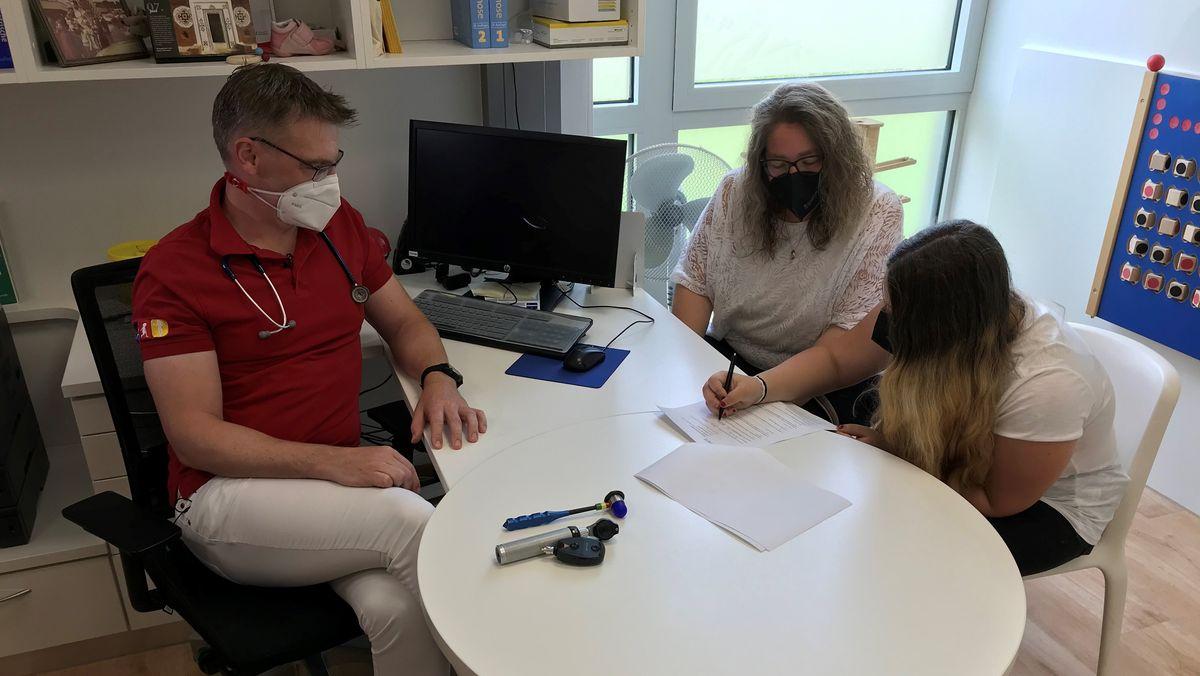 Nathalie willigt in einem Arztzimmer zu ihrer Corona-Impfung ein.