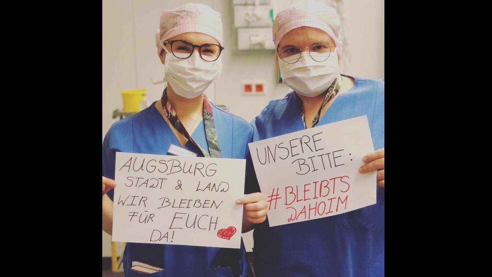 """Krankenschwestern mit Schildern in der Hand, auf denen steht: """"Wir bleiben für euch da. Unsere Bitte: Bleibts dahoim!"""""""