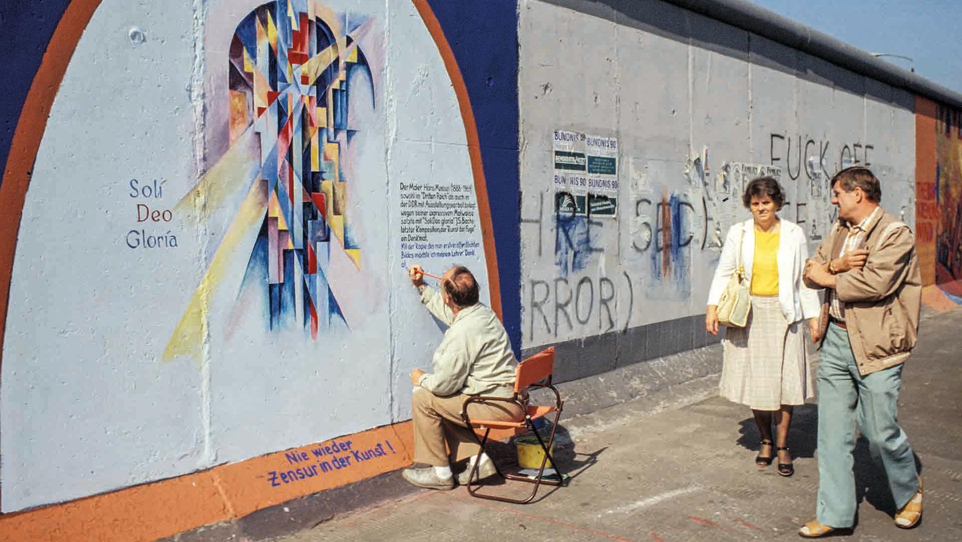 """Ein älterer Herr bemalt die Mauer und schreibt etwas an die Mauer, darunter """"Nie wieder Zensur in der Kunst!"""""""